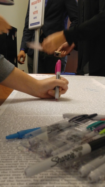 """After the panel discussion, attendees were invited to sign a copy of the Constitution with their own """"John Hancock."""""""